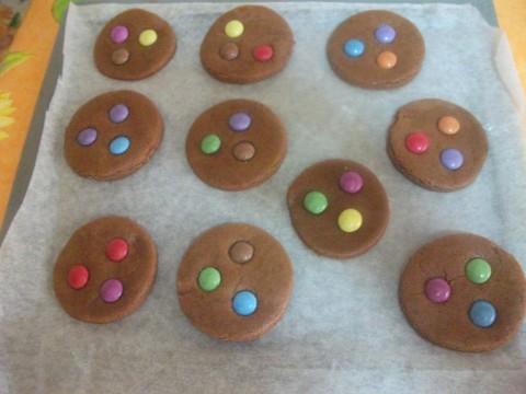 Avvolgere la sfera nella pellicola trasparente e farla riposare in frigo per 30 minuti, poi stenderla e ricavare i biscotti aggiungendo 3-4 smarties per biscotto.