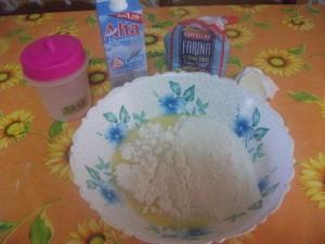 In una ciotola versiamo il latte, un cucchiaio di burro sciolto, la farina e un pizzico di sale.