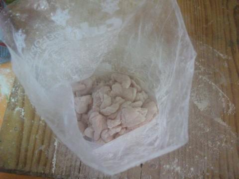 Tagliare a pezzettini le 5-6 fettine di petto di pollo, riporle in una bustina, mettere all'interno di essa una manciata di farina e agitare per far infarinare tutti i pezzettini di pollo.