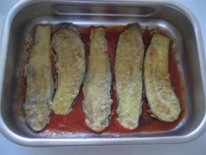versare 2 mestoli di salsa nella tegia e adagiare il primo strato di melanzane
