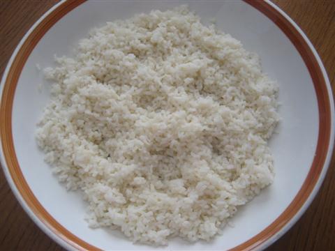 Portate a ebollizione un litro di acqua, salatela, unite il riso e cuocetelo per il tempo indicato sulla confezione. Quando è cotto scolatelo, passatelo sotto l'acqua fredda, lasciatelo sgocciolare molto bene e rovesciatelo in una ciotola.