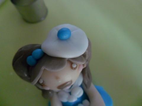 Con un cerchietto di pdz bianco creare un cappellino da posizionare sopra la testa con un pallino piccolissimo applicato sopra.