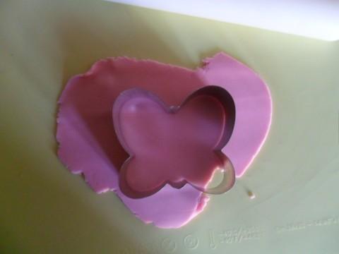 Prendere un pezzetto di pdz del colore che preferite, in questo caso rosa. Stenderlo col mattarello molto sottile. Se tende ad appiccicarsi spolverizzare il tavolo con un po' di amido. Tagliare quindi la pdz col tagliapasta usato per tagliare i biscotti.