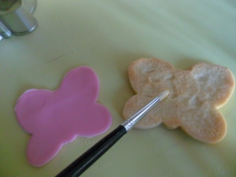 A questo punto abbiamo un biscotto e una forma di pdz della stessa grandezza: come attaccarli? Facile!!Basta spennellare con un pochino di miele (o di marmellata se volete!) il biscotto in modo che sia appiccicoso...una sorta di collante per la pasta di zucchero!