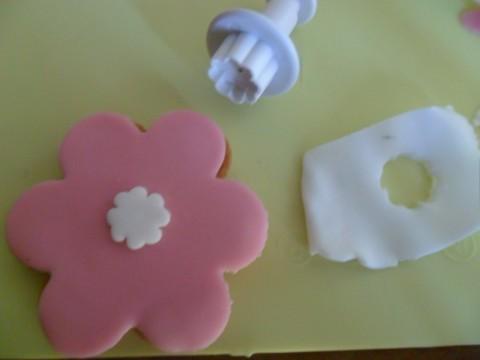 Adesso decoriamo il biscotto a forma di fiore: ritagliate un piccolo fiorellino con la pdz bianca e applicatelo al centro.