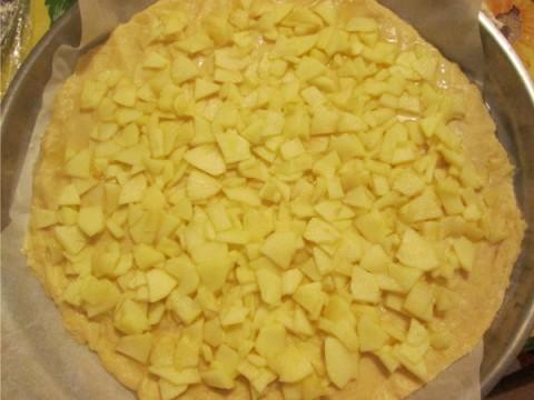 Stendete una parte dell'impasto aiutandovi con un mattarello. Imburrate e infarinate lo stampo (oppure coprite con carta da forno), foderate la tortiera con la pasta frolla e distribuite le mele.