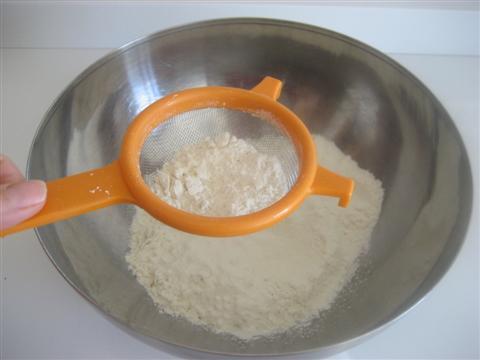 In un'ampia ciotola setacciare la farina,