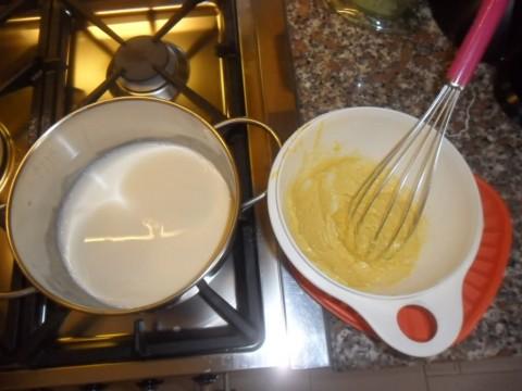 In un pentolino riscaldare il latte, a parte in una ciotola mescolare i tuorli con lo zucchero, sbattere per bene, aggiungere la farina setacciata e continuare a mescolare.