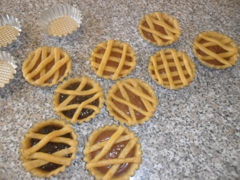 Trascorso il tempo necessario, prendere le formine versare la marmellata o la nutella, in ultimo disporre le strisce sulla superficie. Infornare e cuocere per circa 30 minuti.