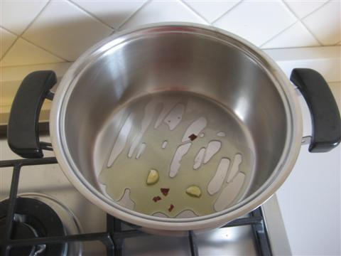In una padella far rosolare l'aglio e il peperoncino nell'olio