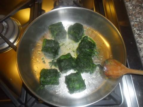 In una pentola far rosolare l'aglio tagliato a pezzetti nell'olio, aggiungere gli spinaci a cubetti