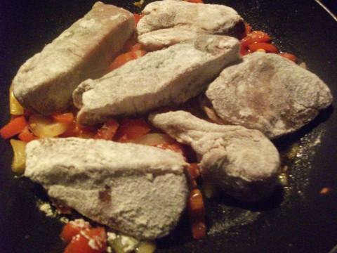 Preparate la salsa con olio, cipolla e pomodorini tagliati in 4 (se risulta asciutta aggiungete 1/4 di bicchiere di acqua). Quando la salsa è pronta adagiate sopra i filetti infarinati.