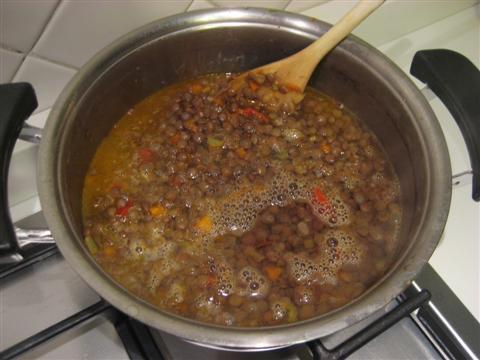 Versare le lenticchie e dell'acqua calda fino a coprire le lenticchie, mescolare con un mestolo di legno e cuocere fin quando le lenticchie saranno appena cotte. Mescolare di tanto in tanto.