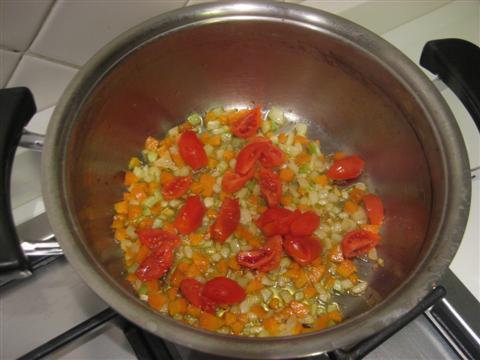 In un'ampia pentola far rosolare leggermente la cipolla tagliata a pezzettini nell'olio, aggiungere le carote e il sedano lavati e tagliati a pezzetti piccoli. Far cuocere per circa 5 minuti e aggiungere i pomodorini tagliati in 4 parti. Cuocere per altri 2-3 minuti.