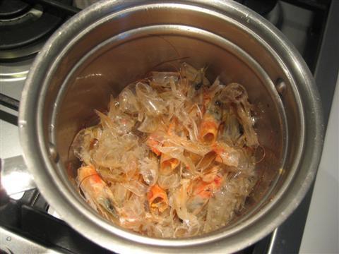 Preparare il fumetto. In un pentolino far rosolare l'aglio nell'olio, quando sarà leggermente imbiondito toglierlo e aggiungere le teste e i gusci dei gamberi