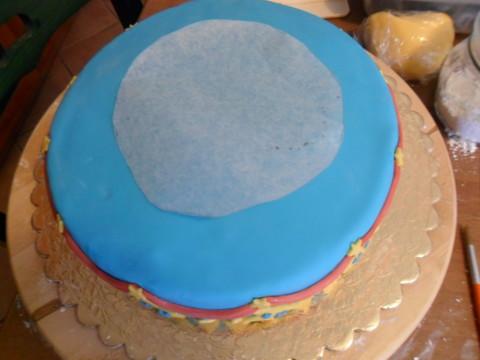 Prendete la sagoma di carta forno e adagiatela al centro della prima torta, la base. Con gli stuzzicadenti lievemente incidete il contorno.