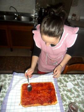 Togliere dal forno il dolce e rovesciarlo sul tavolo. Cospargere di marmellata e