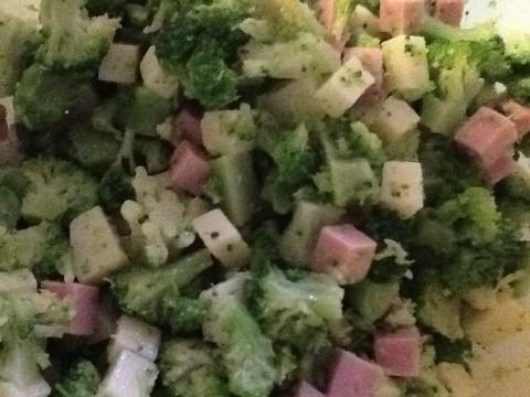 Riducete i broccoli a tocchetti piccoli e aggiungete il prosciutto e il formaggio a cubetti. Salate moderatamente e pepate a piacere, unite tre cucchiai di olio extravergine d'oliva e mescolate bene.
