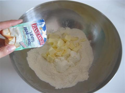 aggiungere il burro tagliato a pezzetti (tenuto precedentemente a temperatura ambiente), la ricotta e mezza bustina di lievito setacciata.