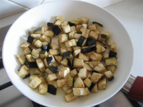Lavare e tagliare la melanzana a quadrotti, in una padella aggiungere un pò d'olio extravergine d'oliva (4 cucchiai), farlo leggermente riscaldare e aggiungere le melanzane ( le melanzane assorbiranno l'olio, quindi bisogna aggiungere un pò di acqua tiepida e far cuocere per circa 10 minuti a coperchio chiuso).