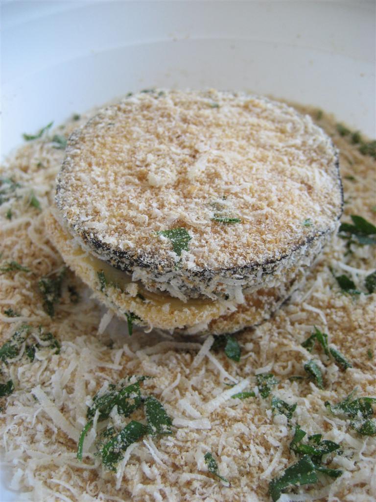 Passare le fette prima nell'uovo leggermente sbattuto con un pizzico di sale e poi nel composto preparato precedentemente