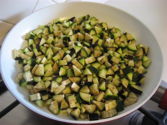 Lavare e tagliare le zucchine e le melanzane a cubetti. In una padella far imbiondire leggermente la cipolla tagliata a pezzettini in 4 cucchiai di olio extravergine d'oliva. Aggiungere gli ortaggi e un bicchiere di acqua tiepida.