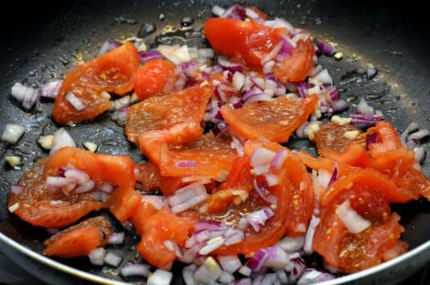 Una volta che le nostre verdure saranno pronte per la cottura, tritate aglio e cipolla e fateli appassire in una padella con 2 cucchiai di olio. Unitevi poi i pomodori e cuocete per 10-15 minuti.