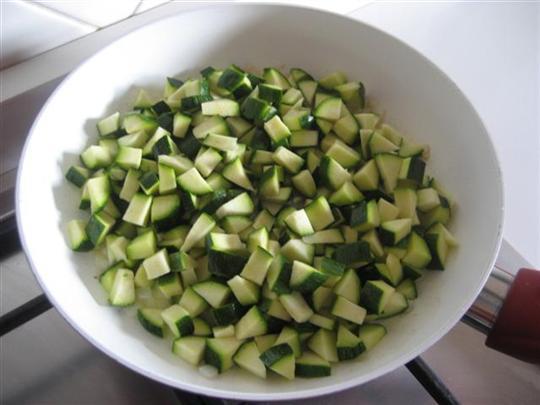 Lasciare leggermente imbiondire la cipolla tagliata a pezzetti nell'olio, aggiungere le zucchine precedentemente lavate e tagliate a dadini.