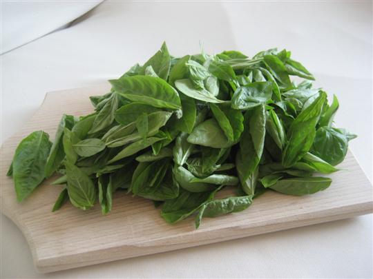 Lavare e asciugare le foglie di basilico con un canovaccio pulito
