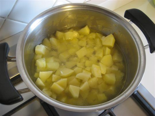 aggiungere le patate precedentemente sbucciate, lavate e tagliate a dadini. Cuocere a fuoco moderato per 2 minuti e con coperchio chiuso. Aggiungere dell'acqua tiepida e continuare la cottura fin quando le patate saranno quasi cotte.