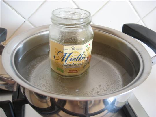 Immergere il barattolo di miele per circa 5 minuti in acqua calda. Girare il miele con un cucchiaino, questo permetterà di velocizzare la fluidificazione.