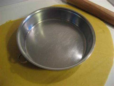 Stendere l'impasto di 3 - 4 mm con il mattarello. Mettere lo stampo sull'impasto e aiutandosi con un coltello tagliare tutto intorno.