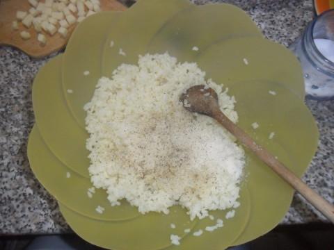 Riponete il riso in una ciotola. Salate e aggiungete il pepe nero (a vostro piacimento), metà del formaggio grattugiato