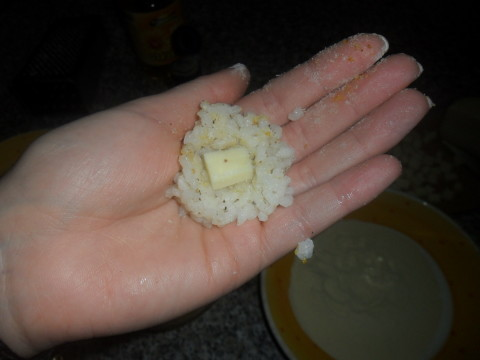 Prendete una piccola porzione di riso, schiacciatela al centro e inserite un pezzetto di provola. Chiudete aggiungendo un altro pò di riso e compattate l'arancino con le mani.