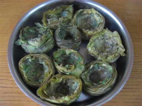 Versare uno o due mestoli di acqua di cottura dei carciofi nella pirofila e disporre i carciofi ben ravvicinati tra loro.